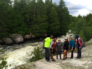 The Ridley Wilderness Youth Program team by beautiful wilderness rapids along a portage in Quetico